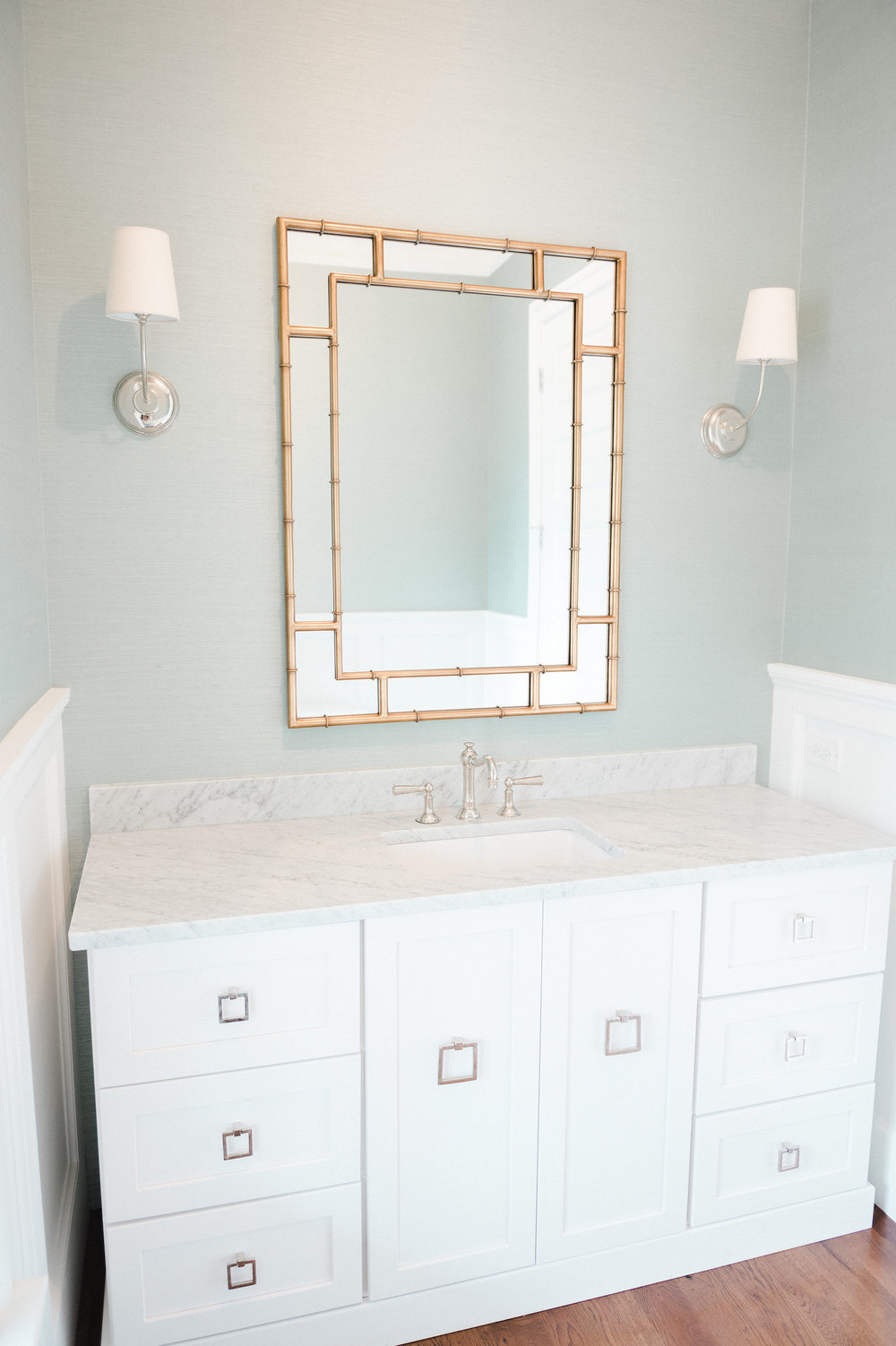 Bathroom sink with gold mirror and white drawers