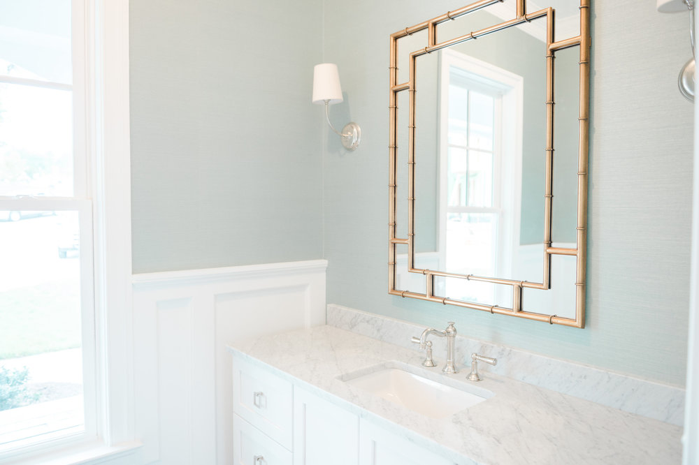 Bathroom mirror with gold trip above sink