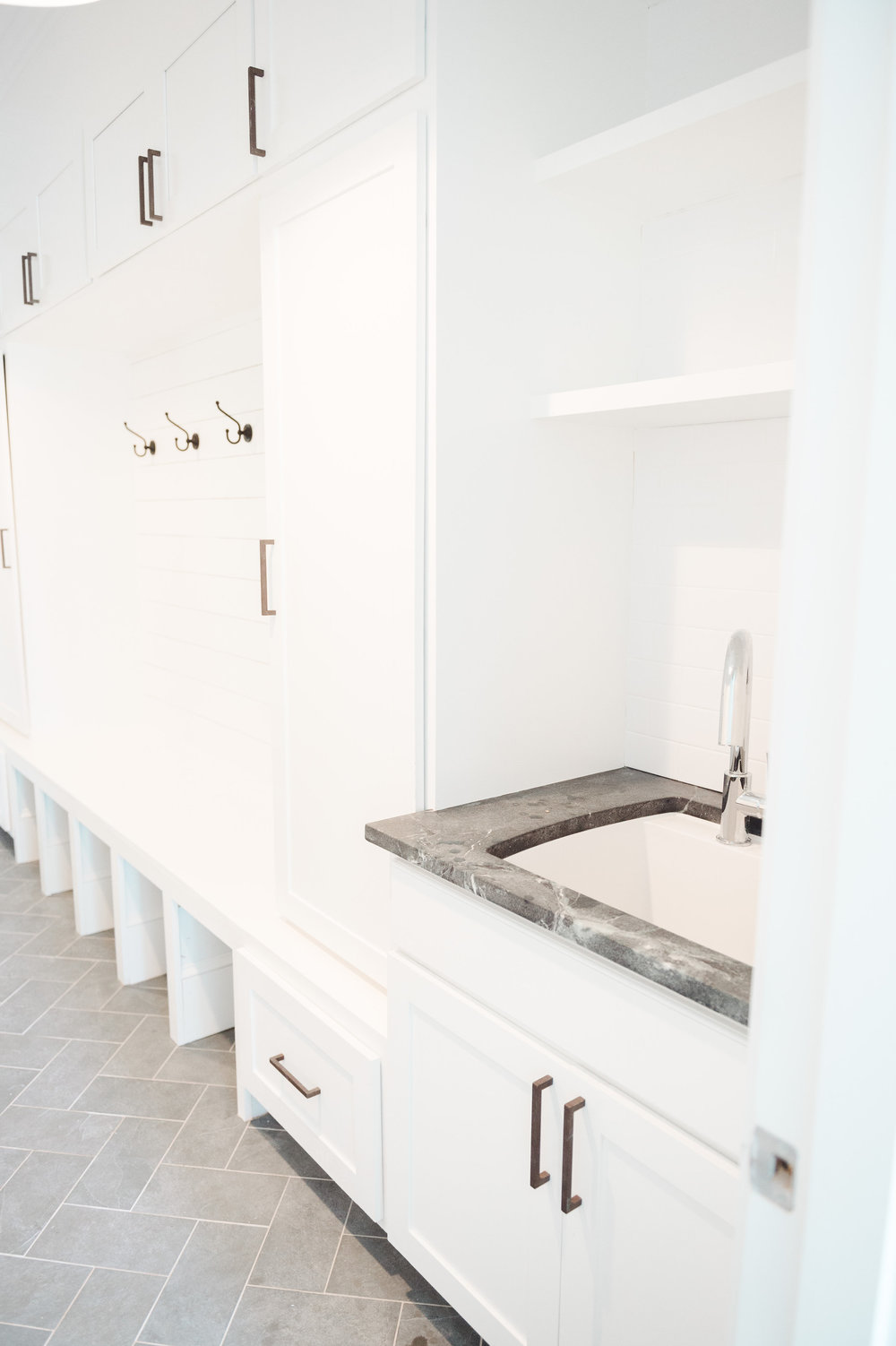 Entry way sink with built-in shoe bins and shelves