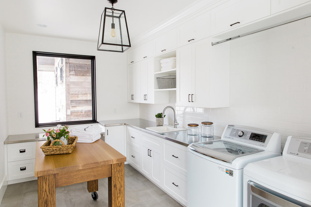 Stainless counters and wood island in laundry || Studio McGee