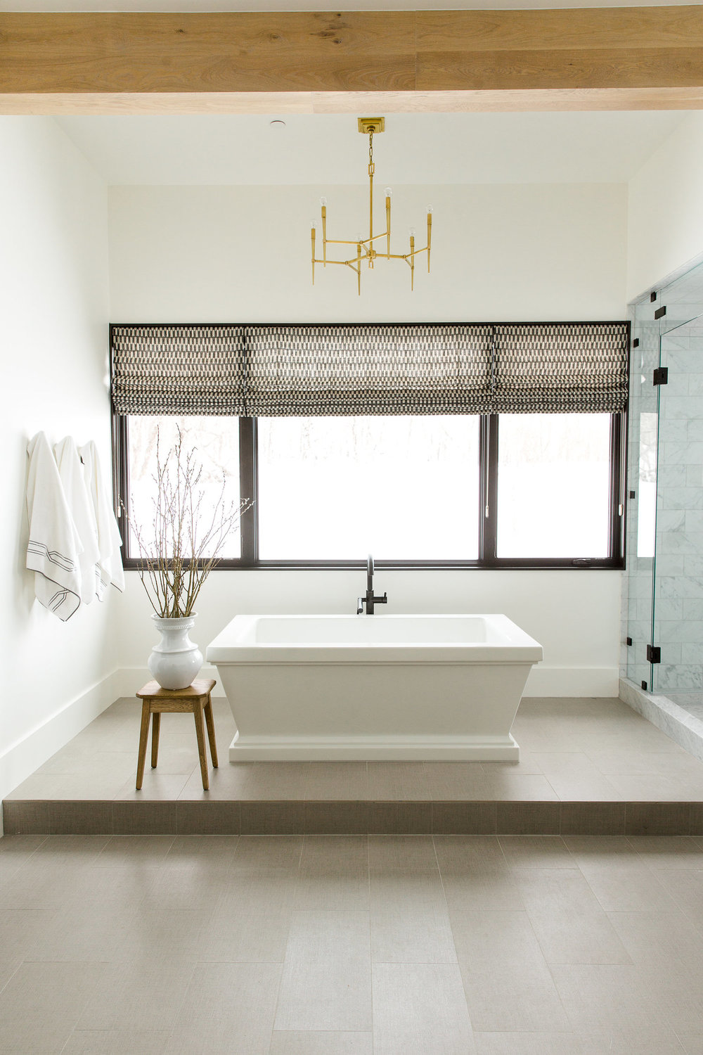 Stand alone porcelain bathtub in front of window