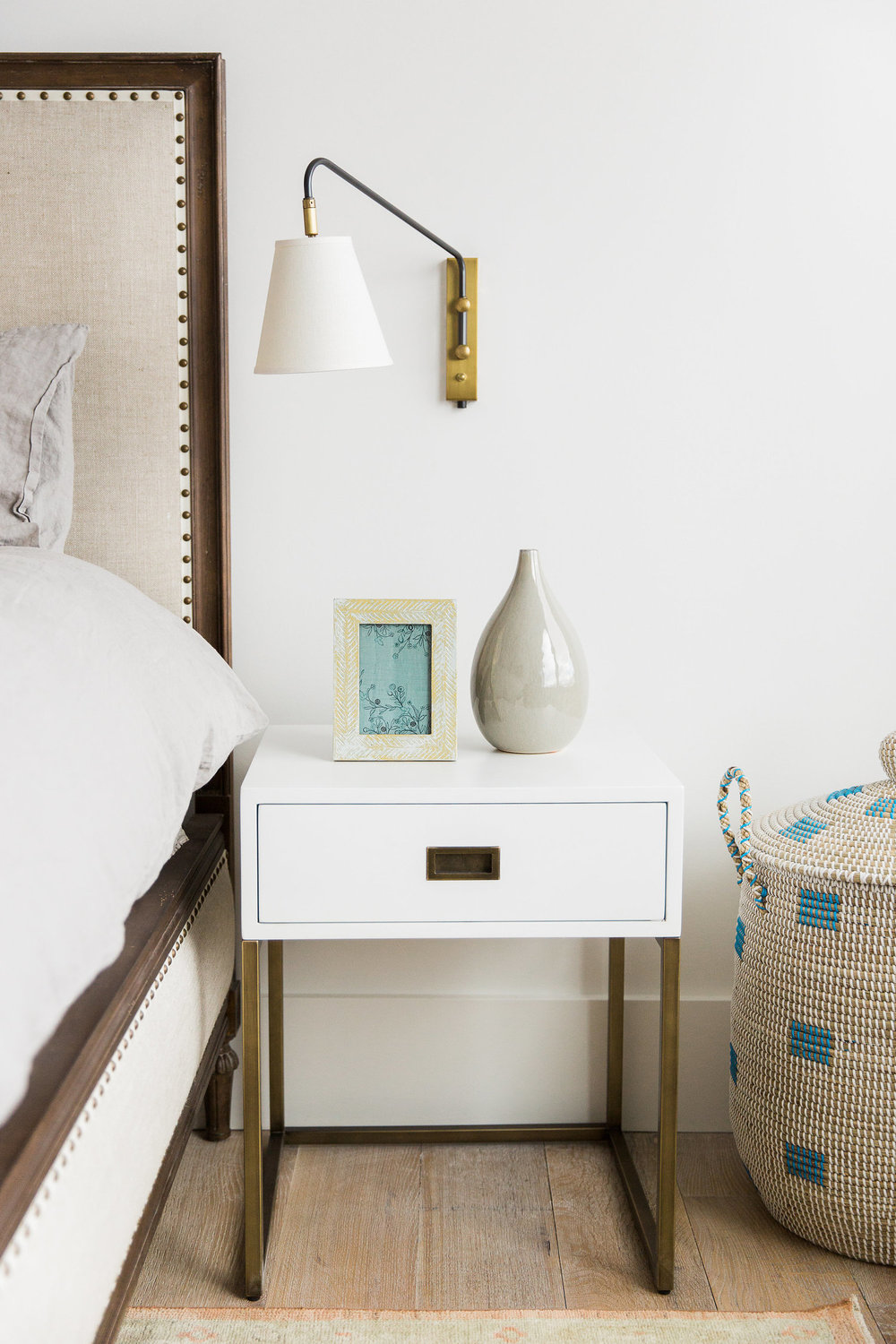 White nightstand beneath mounted lamp