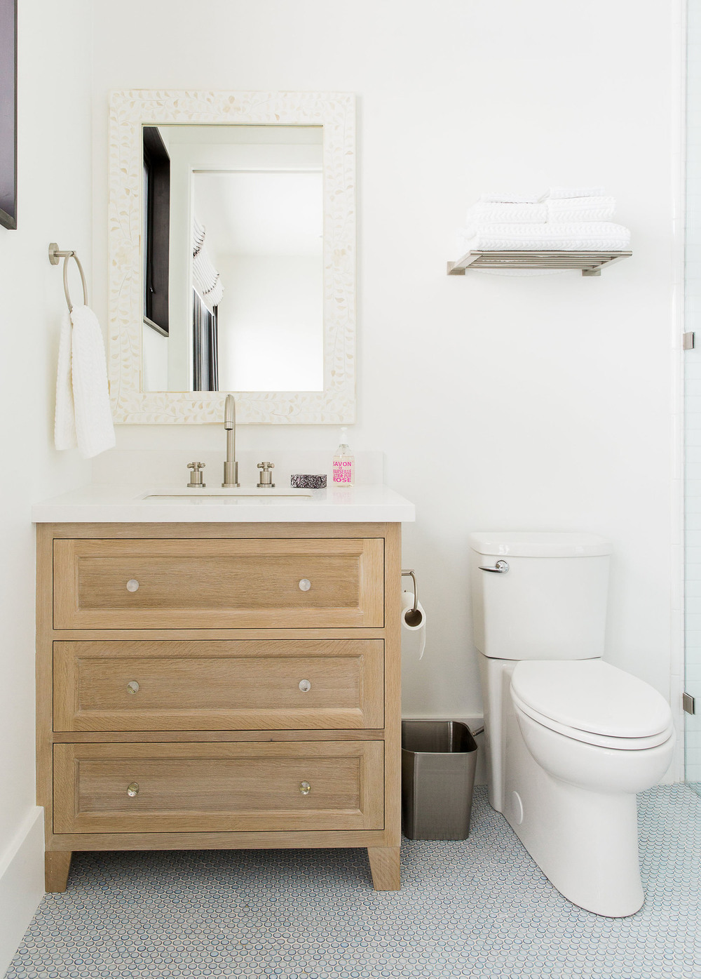 Wooden vanity next to toilet in bathroom