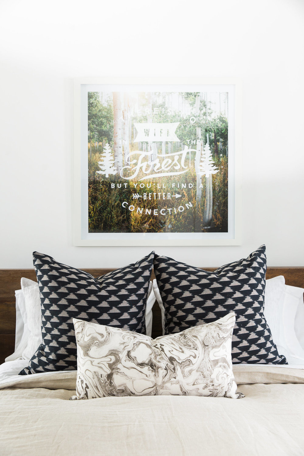 Decorative pillows on bed beneath wall art