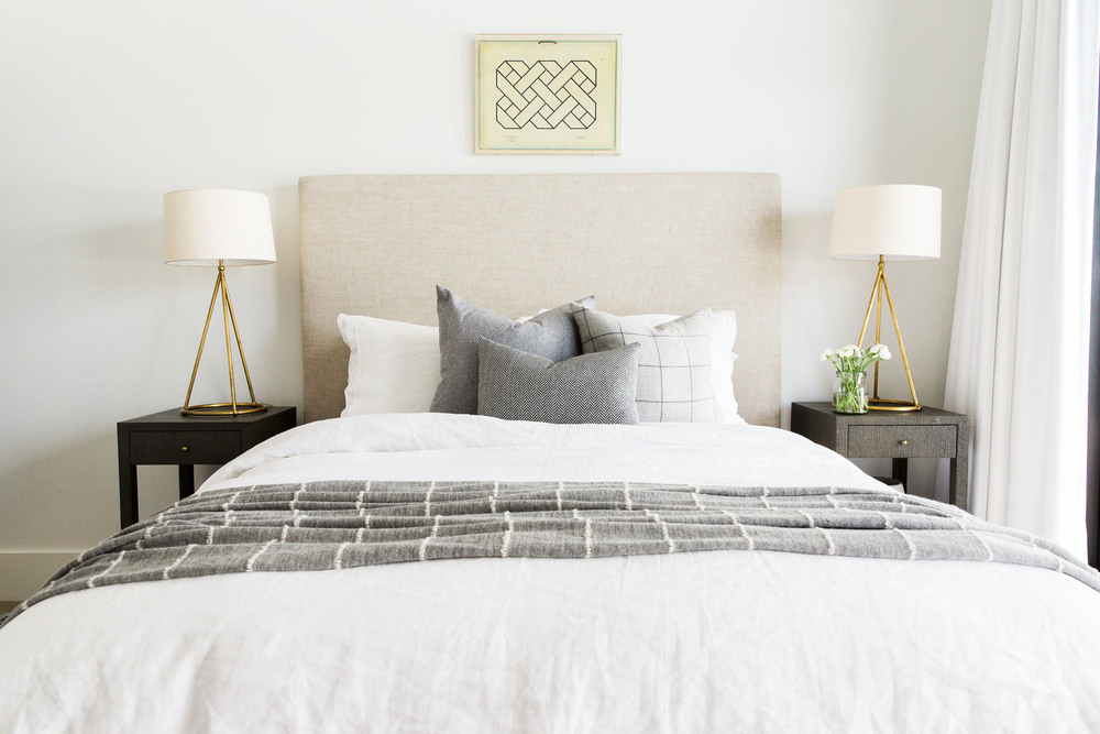 White bed with dark nightstands on either side