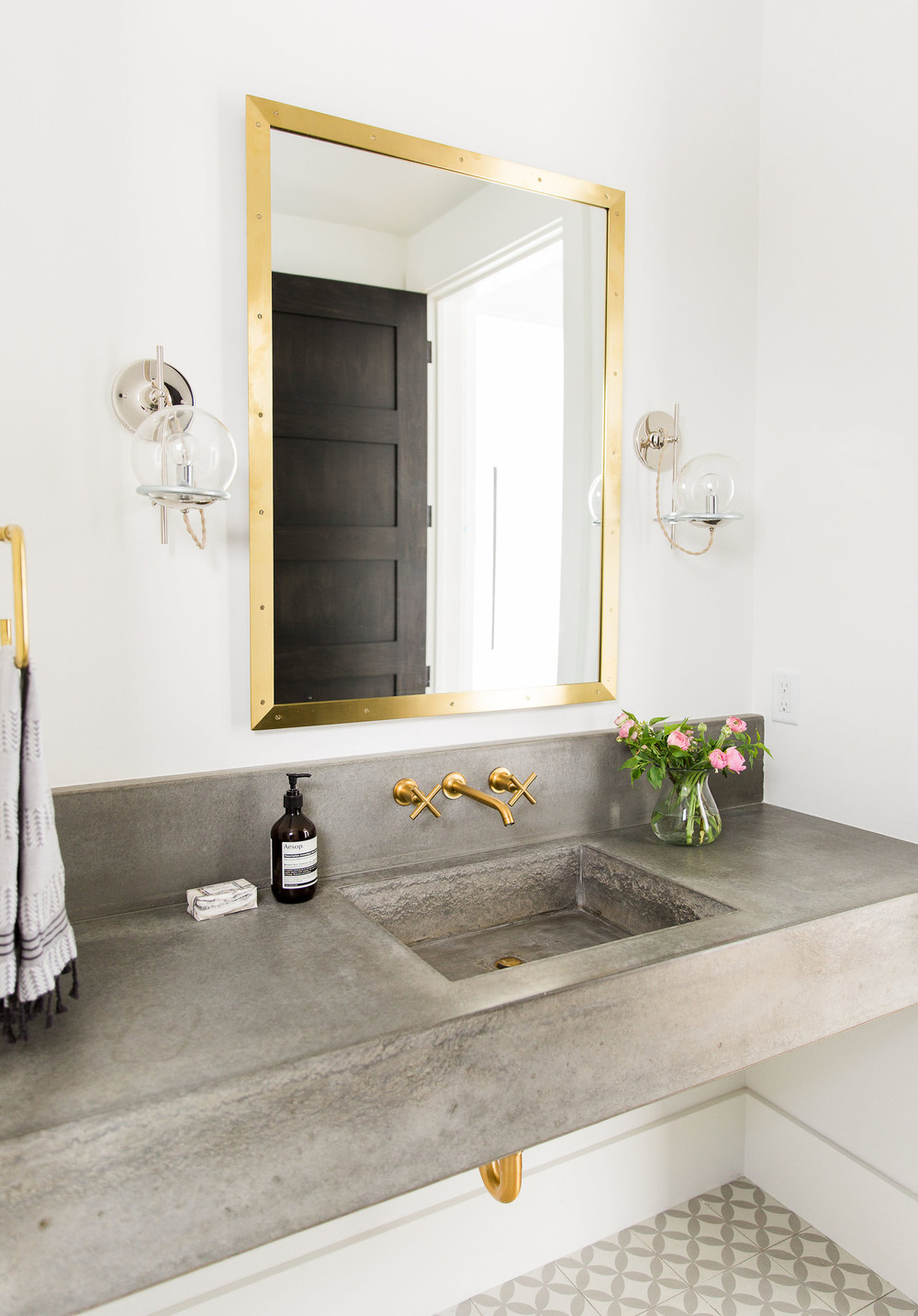 Gold framed mirror above bathroom sink