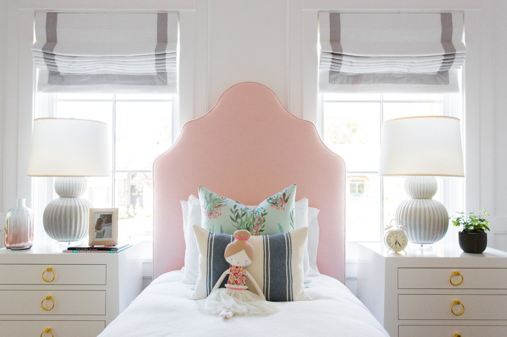 White twin bed with pink headboard