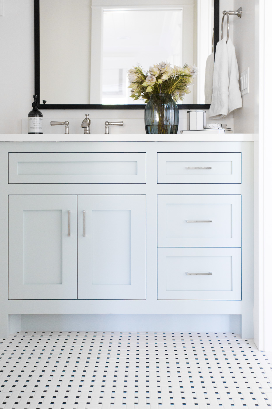 White vanity on small white tiles