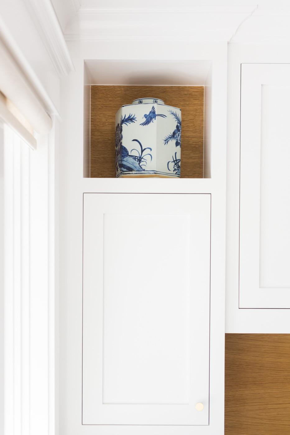 Blue and white jar above side cabinet