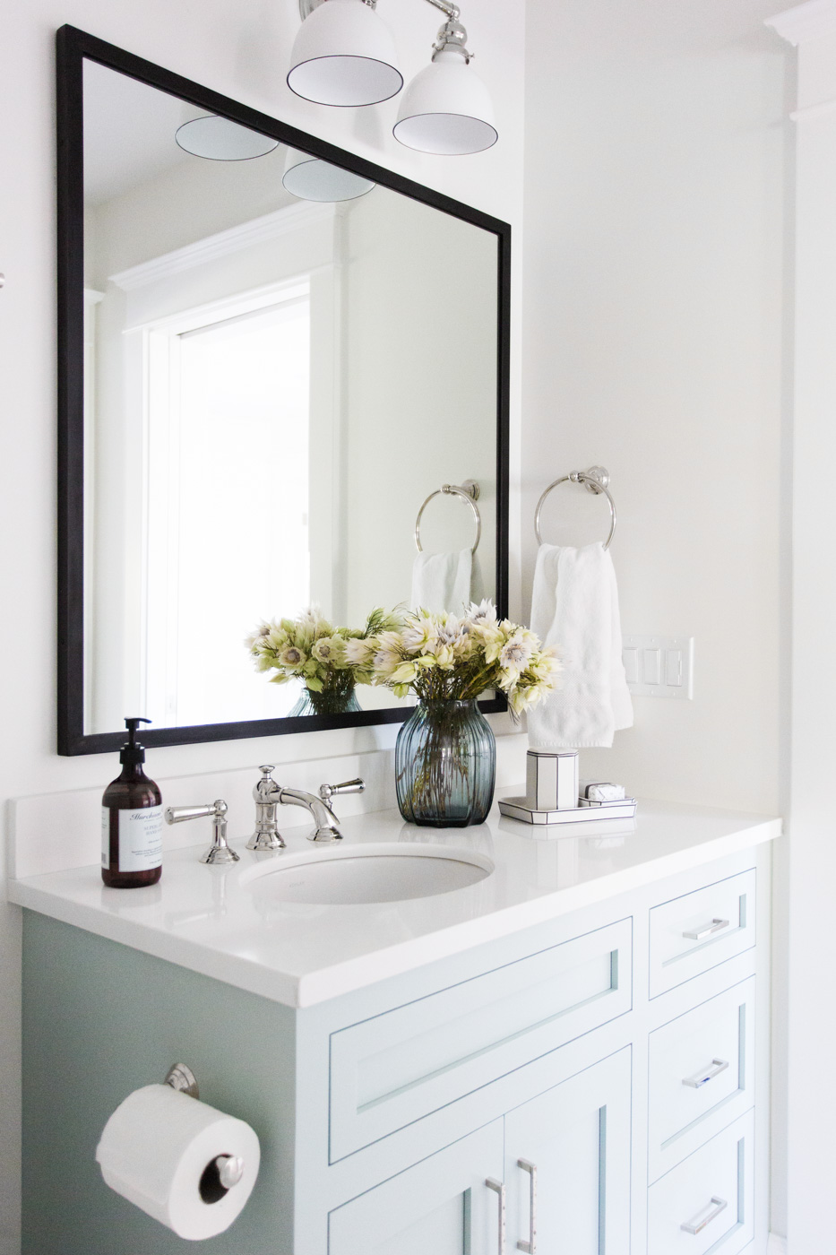 Large mirror behind white bathroom vanity