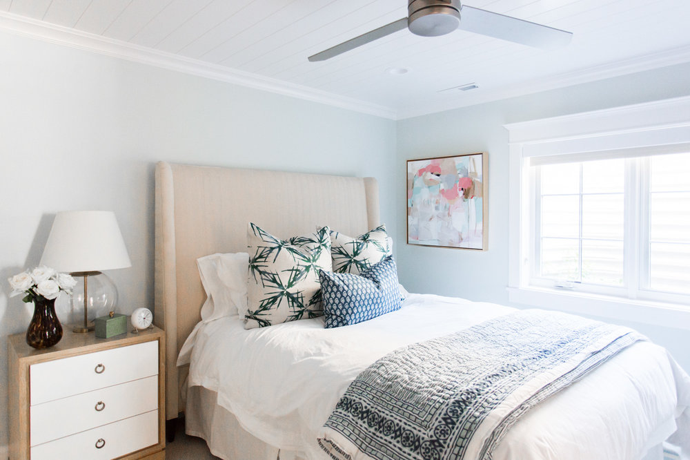 White bed against tan headboard