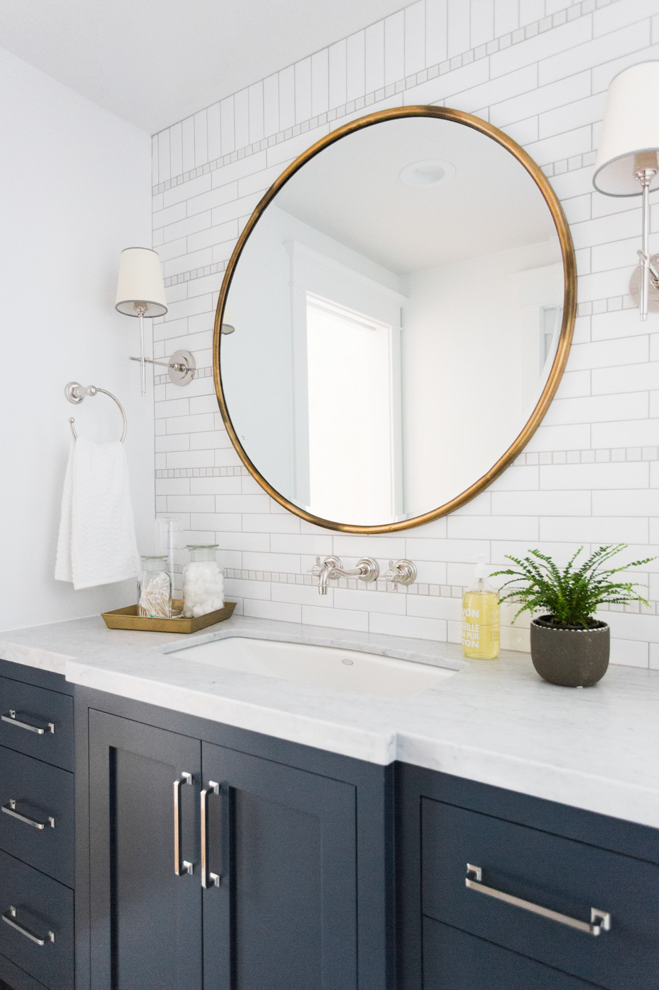Circle mirror against white tile backsplash