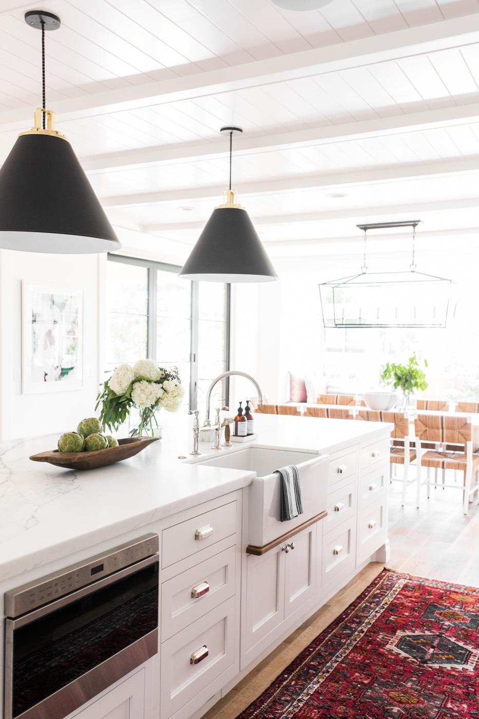 Modern+farmhouse+meets+The+Hamptons+in+Studio+McGee's+latest+remodel+||+vintage+kitchen+rug,+black+cone+pendants,+marble+counters,+farmhouse+sink,+bridge+faucet.jpg