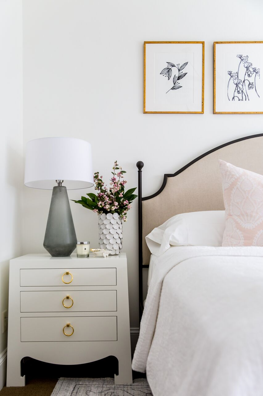 White wooden nightstand beside bed