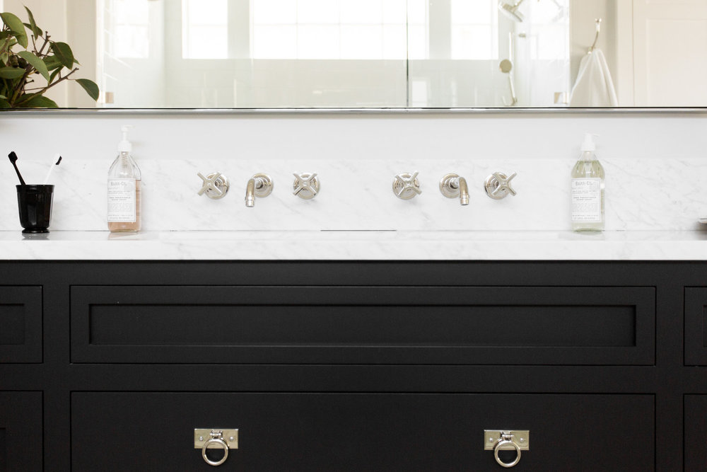 Double faucet mounted on black vanity