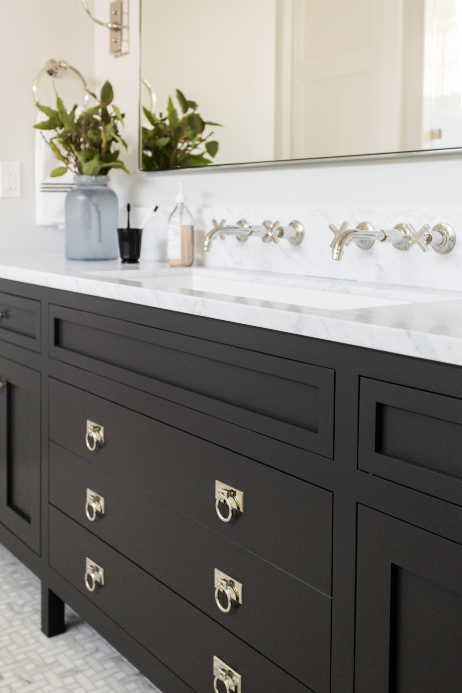 Silver handle details on black bathroom vanity