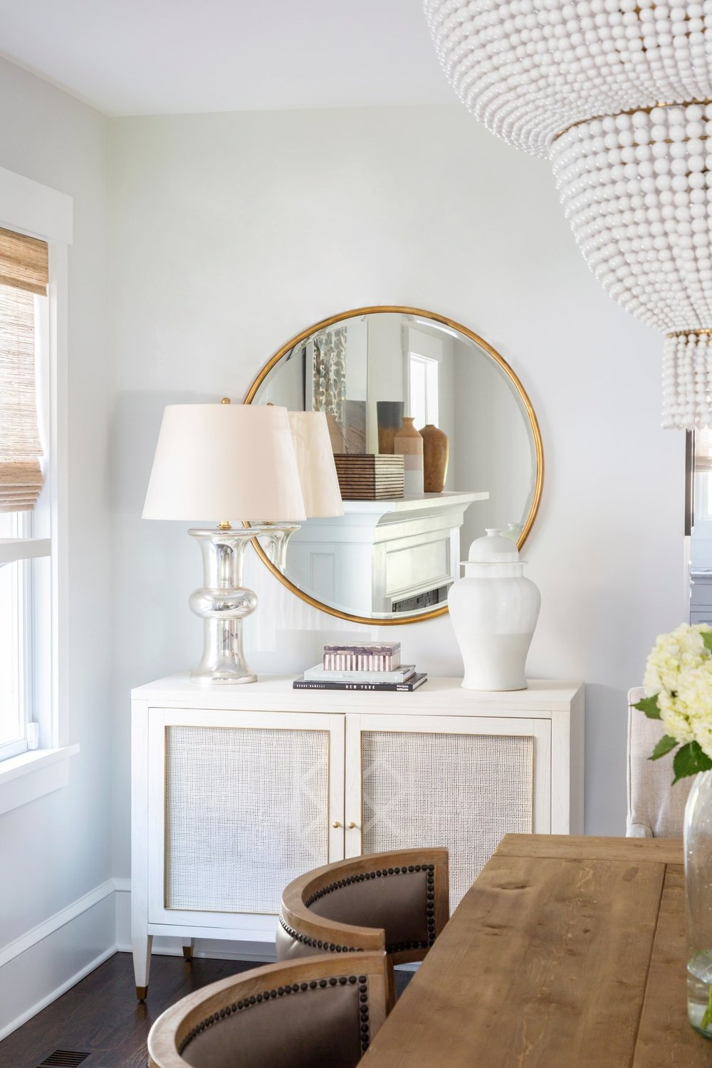Gold circle mirror above white hutch
