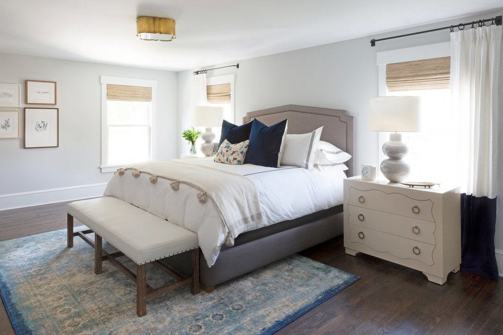 White bed atop a blue area rug