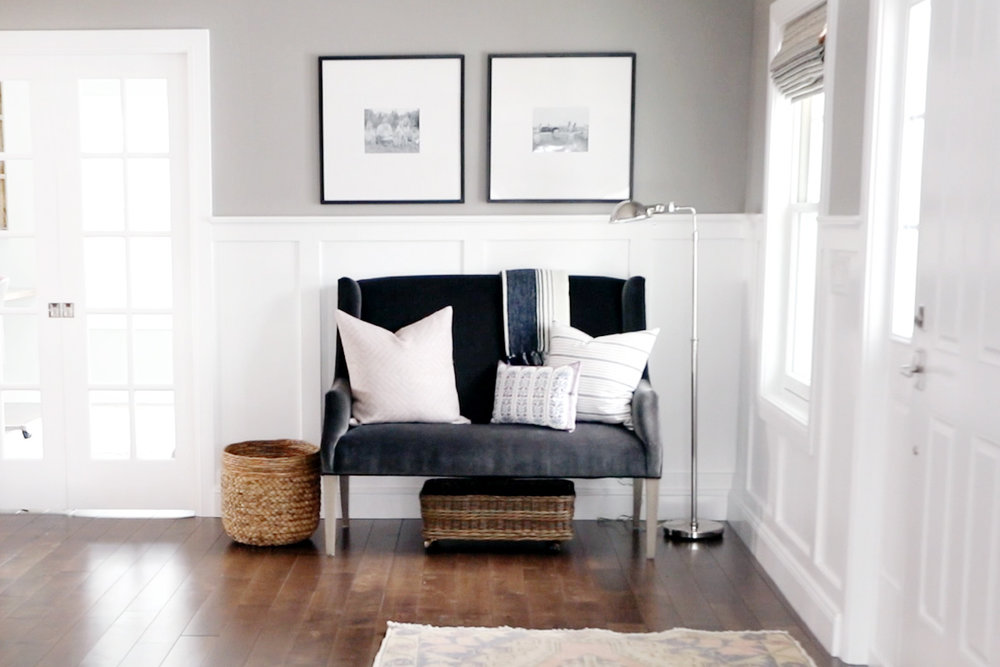 Decorative pillows on grey love seat in entryway
