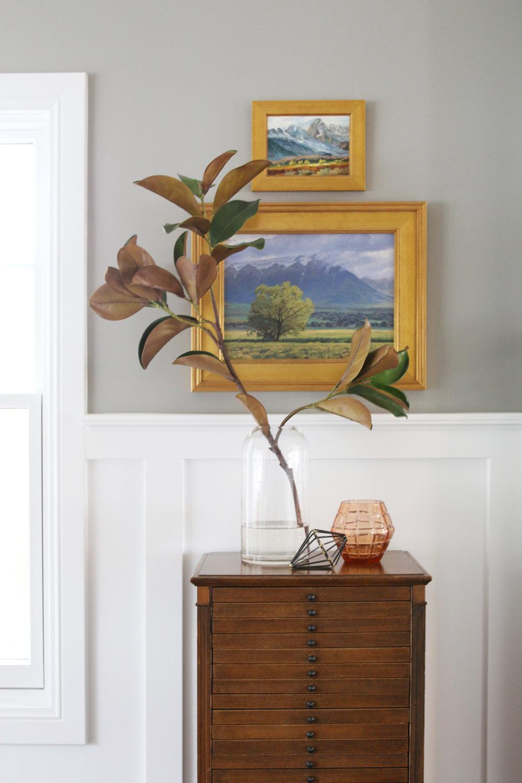 Flower plant in front of gold framed art