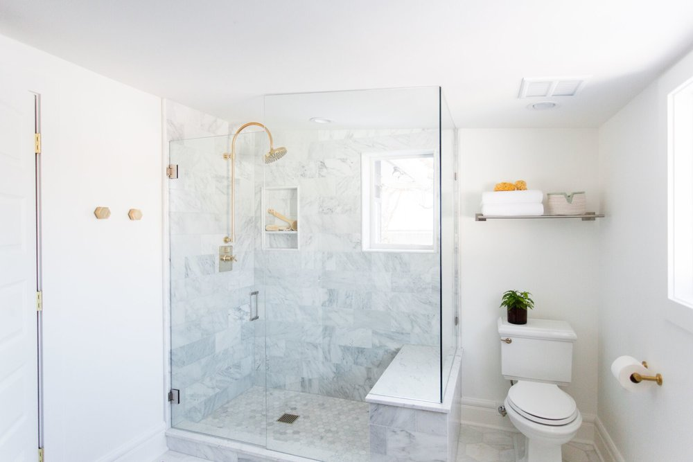 Glass shower and white toilet in bathroom