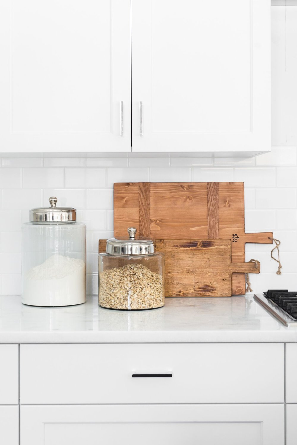 Flour and oat jars on top of white counters