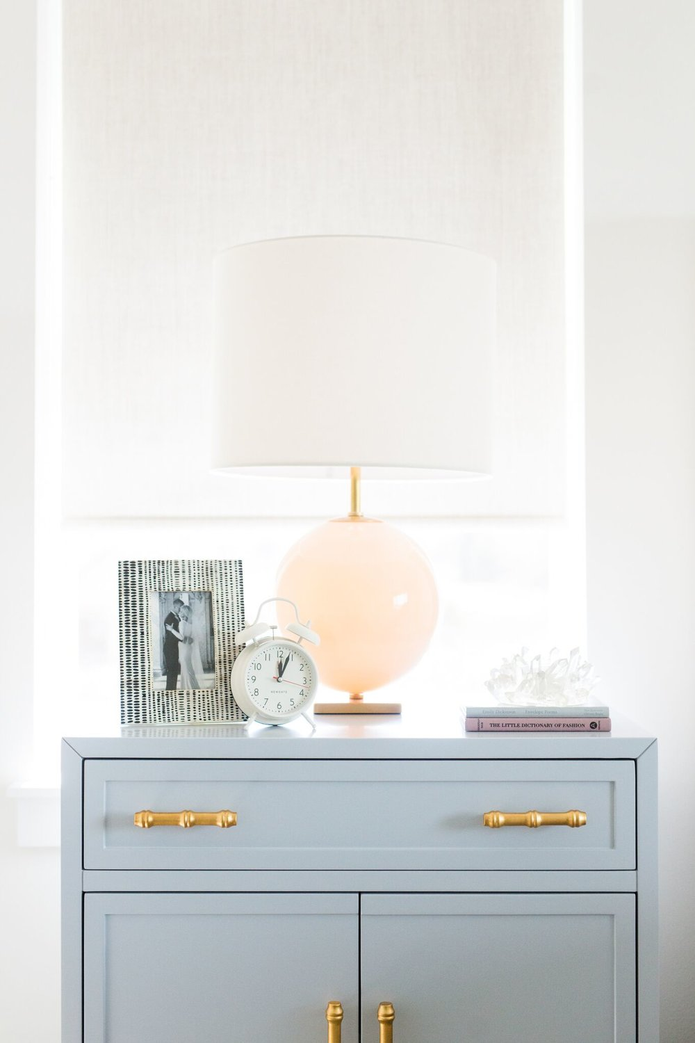 Peach lamp atop blue nightstand