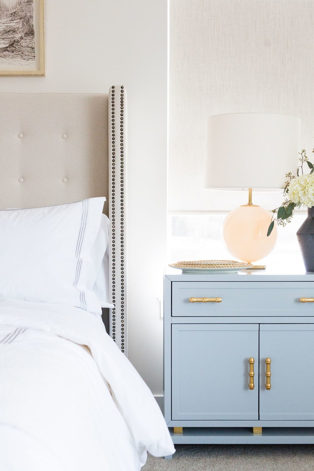 Blue powder nightstand with peach lamp