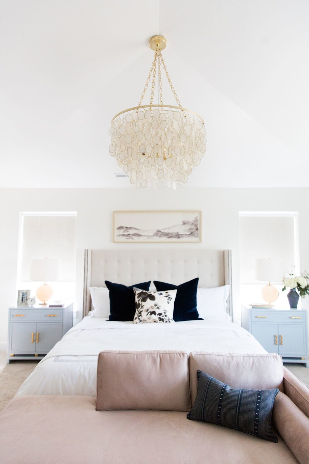 White bed with large white headboard in bedroom