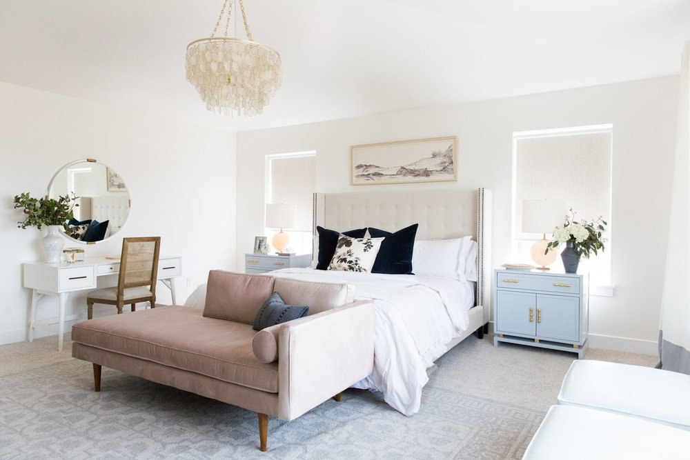 Pink couch at foot of white bed in bedroom