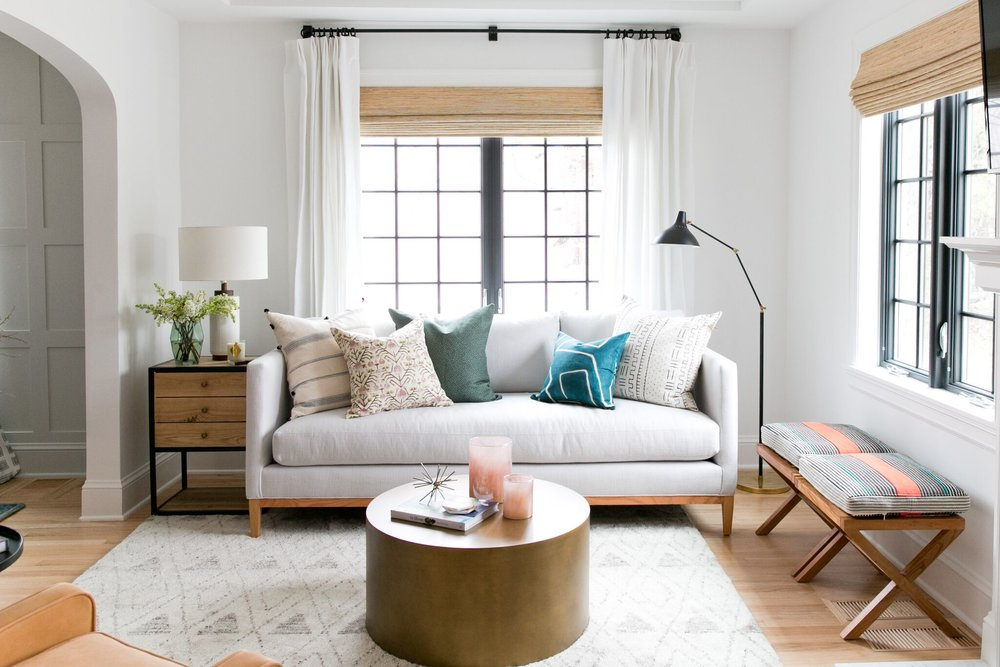 Bright, eclectic living room with black windows in Benjamin Moore's Black Iron, and a white couch with mixed pillows.