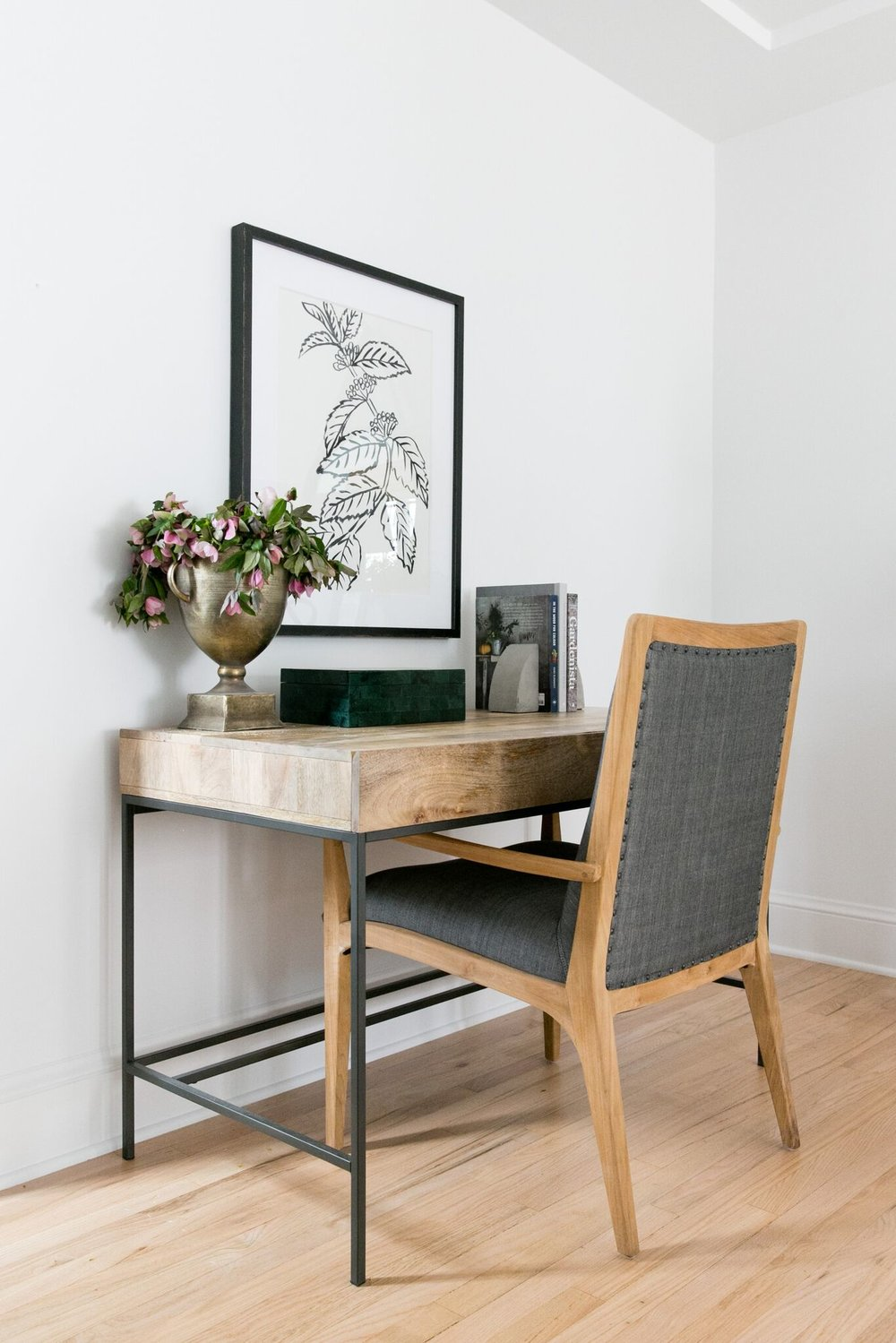Metal and wood desk with beautiful wall artwork.