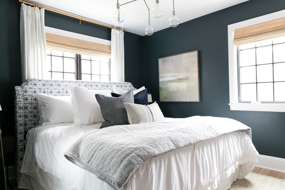 Bold blue-green bedroom in Benjamin Moore's Newburg Green with fresh mixed pillows.