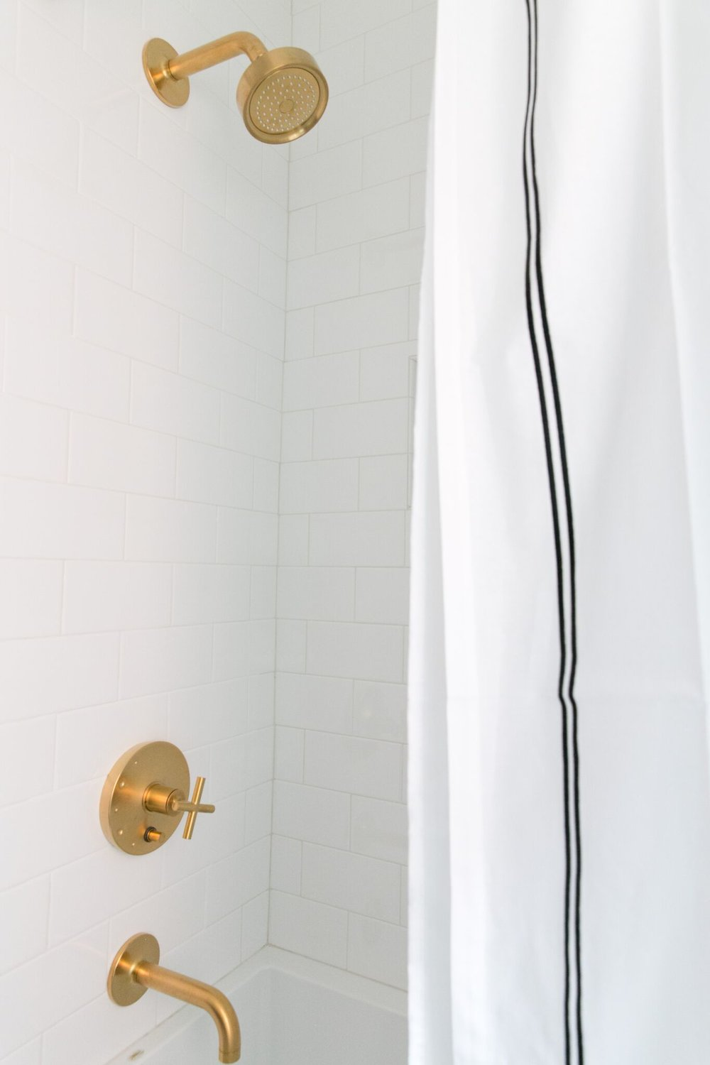 White shower with gold fixtures