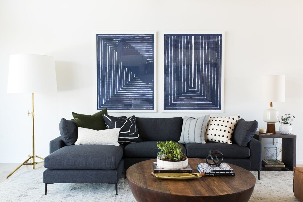 Mid-century great room with modern sectional, round coffee table, and modern artwork.