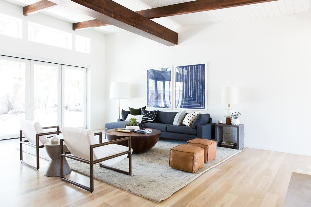 Living room with blue sectional, leather stools, and white chair