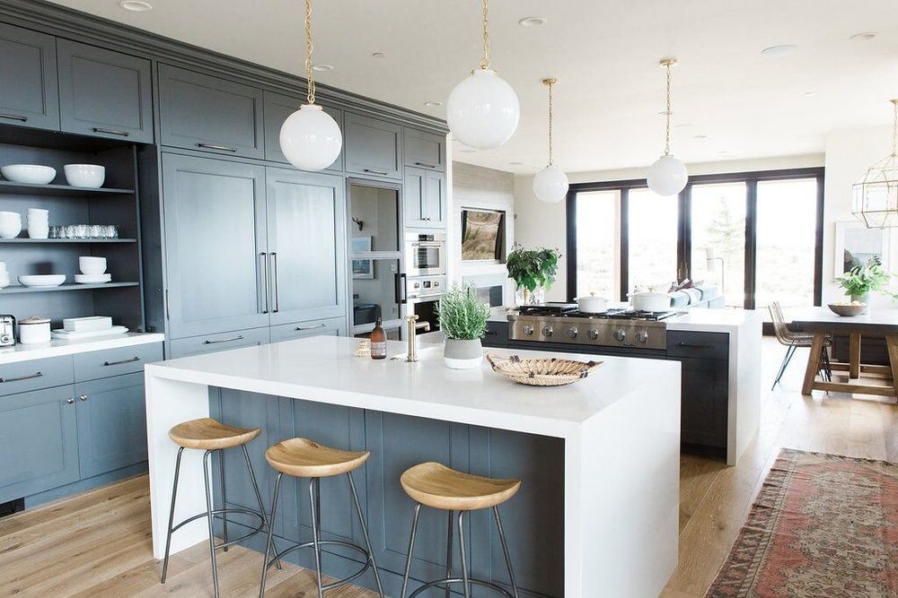 Modern kitchen with white waterfall edged countertops, natural wood barstools, and dark cabinets in Benjamin Moore's Cheating Heart
