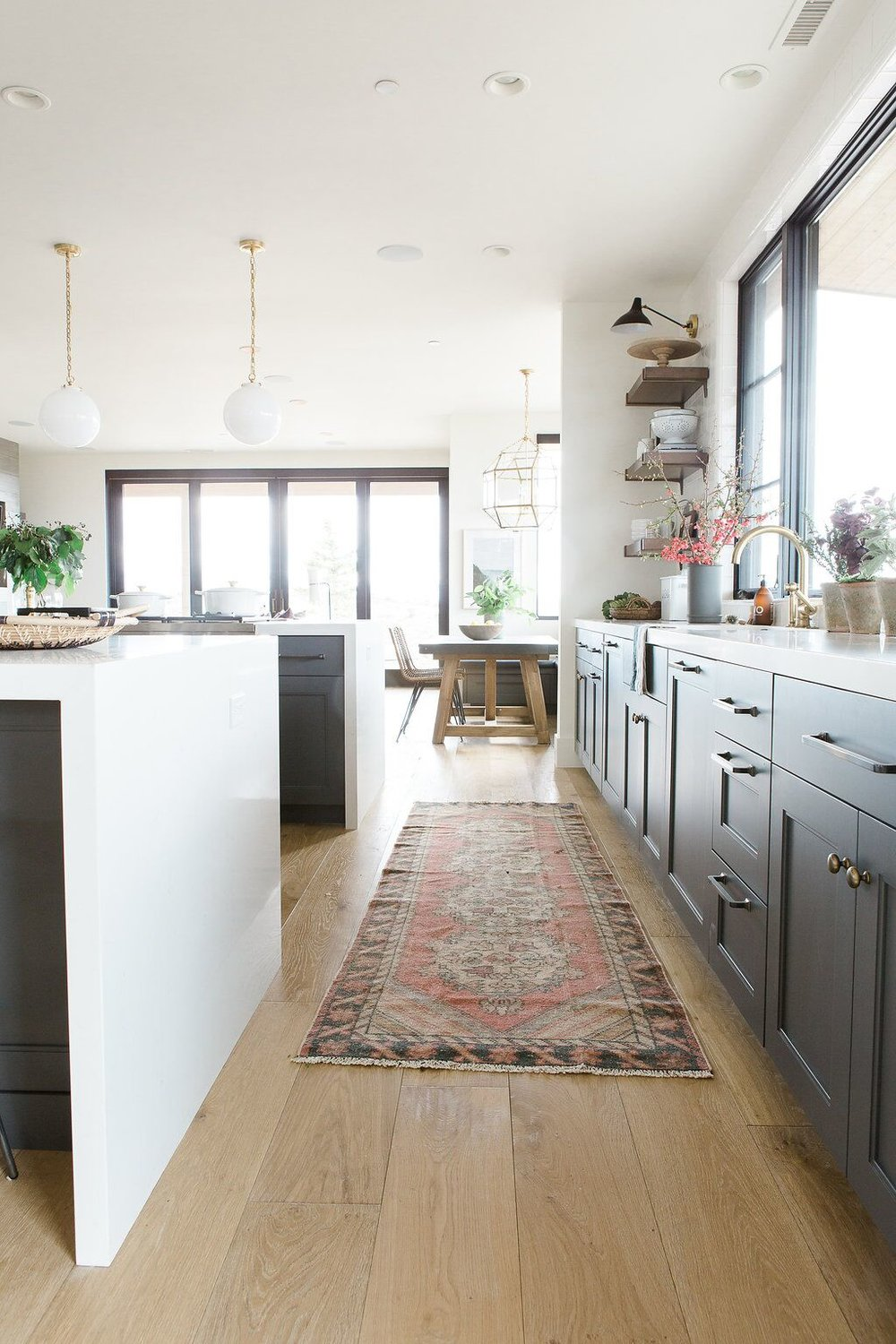 Modern kitchen with deep walnut open shelves, vintage rug and white waterfall edged countertops