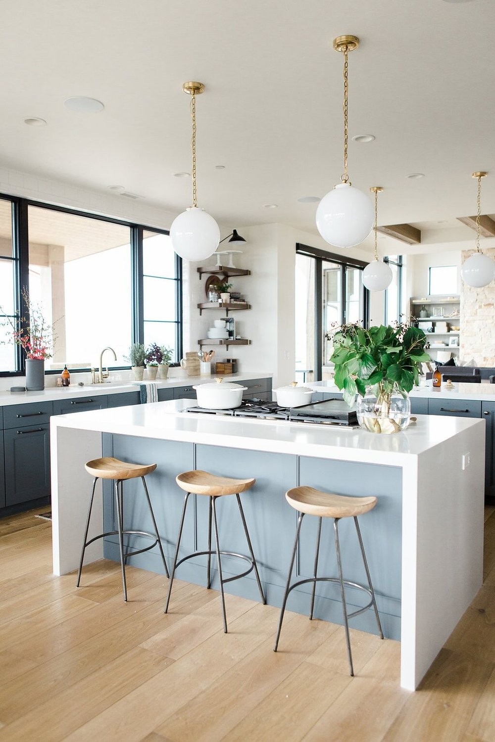 Modern kitchen with open shelves, natural wood barstools, blue cabinets with white waterfall edged countertops