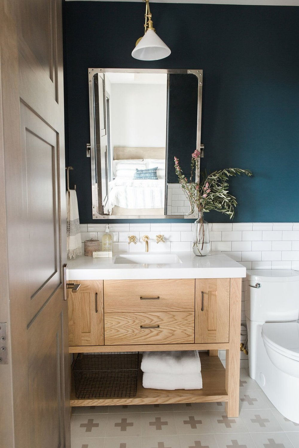 Dramatic and dark bathroom with subway tile and patterned tile floors