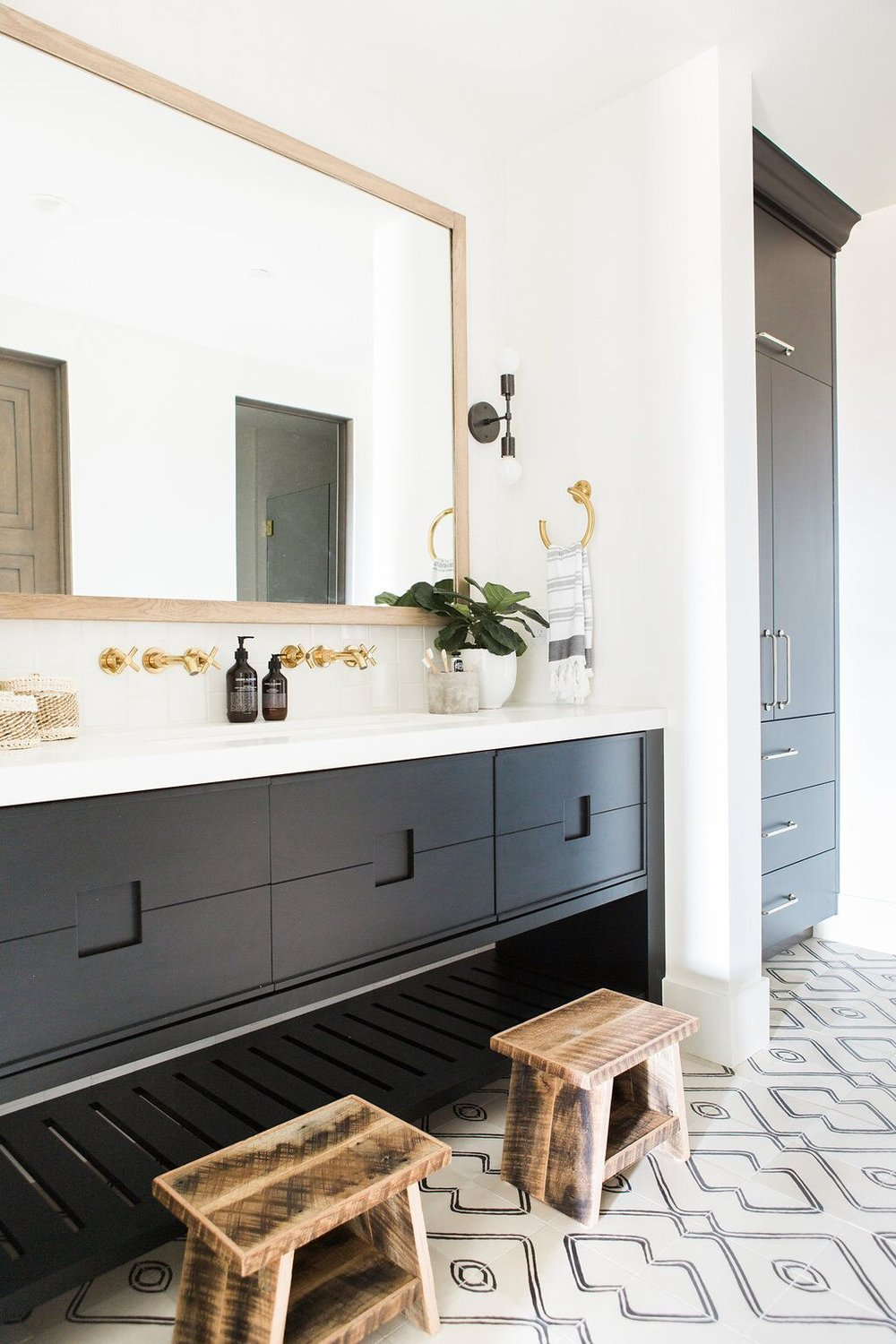 Bathroom with patterned tile, white countertops and gold hardware