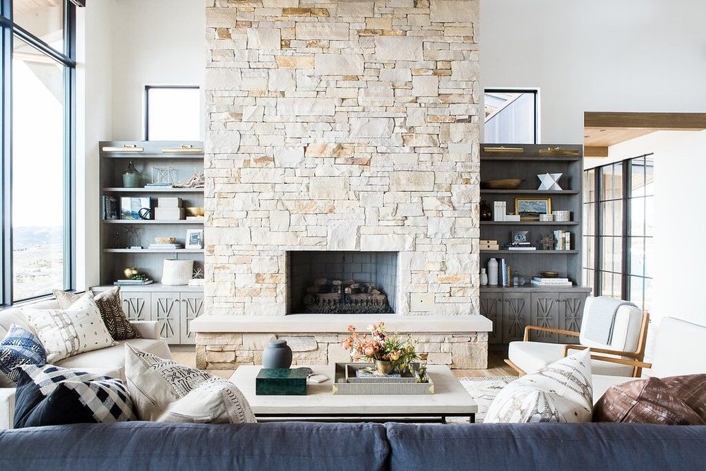 Log fireplace and top of grey couch in living room