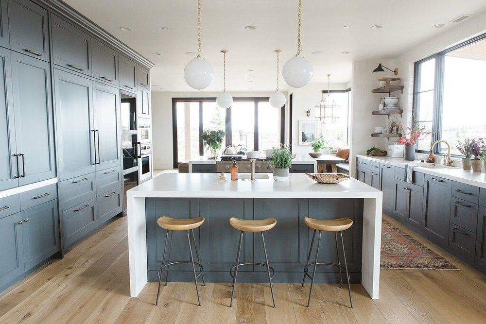 Three wooden stools underneath modern kitchen island
