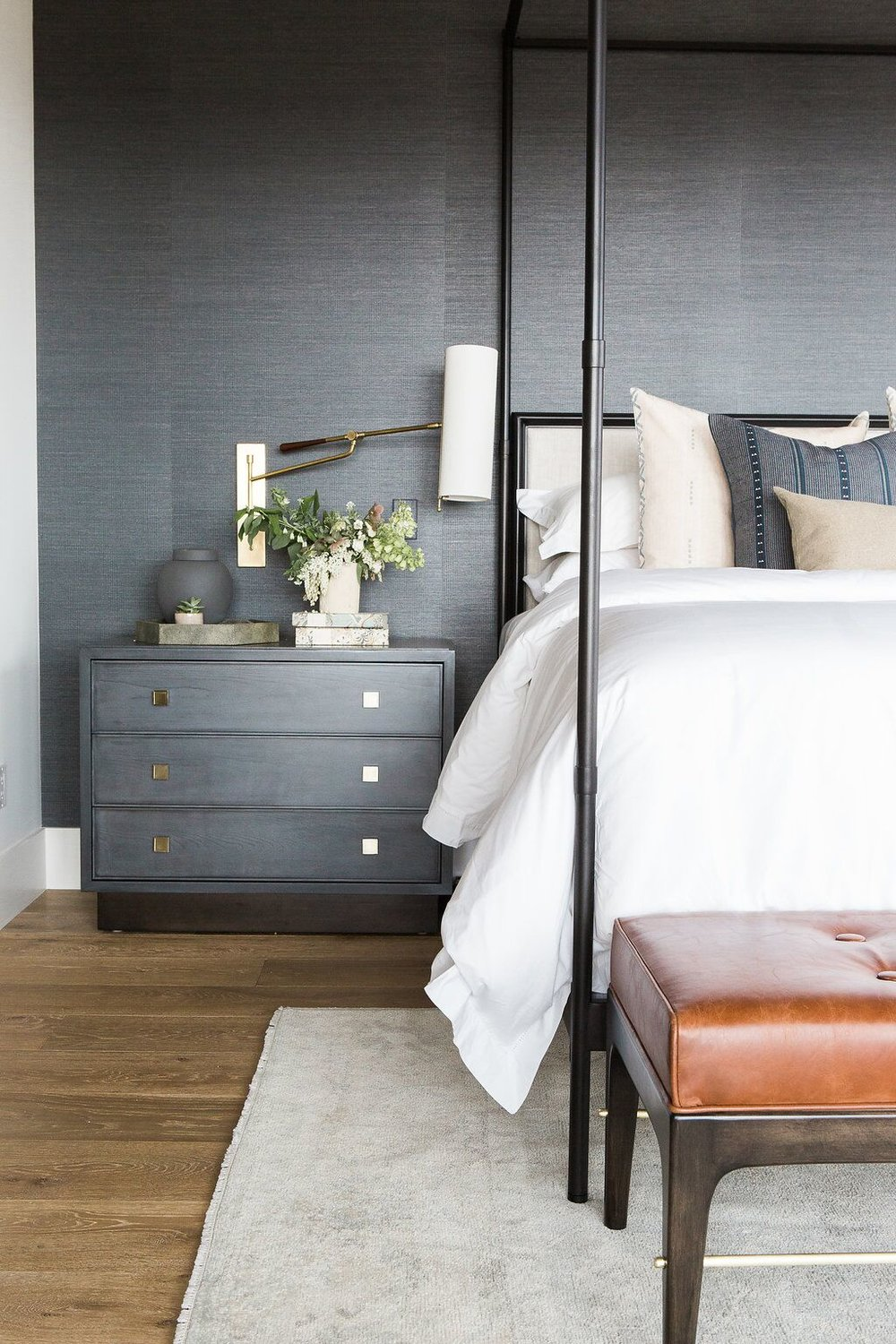 Small grey nightstand on other side of white bed
