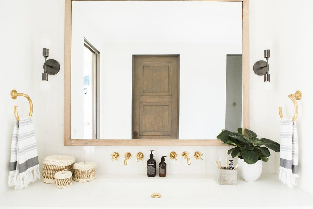 Large mirror behind white vanity in bathroom