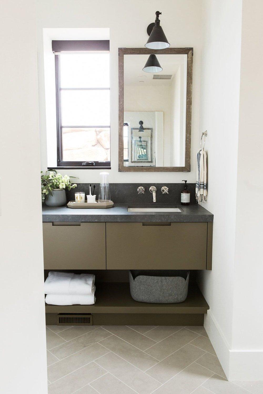 32Guest+bathroom+with+olive+green+cabinets+and+dark+countertops+and+limestone+herringbone+floors.jpg