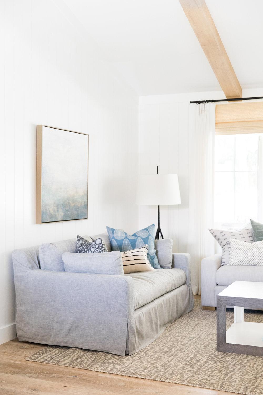 Moody coastal living room with modern art and exposed beams.jpg