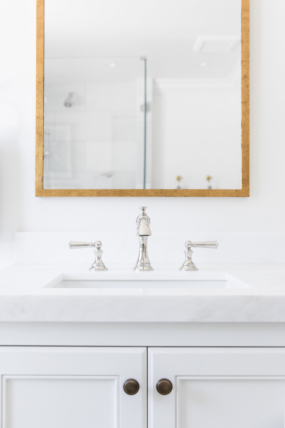 Clean and coastal bathroom with pendant over bathtub, brass and polished nickel decor in bathroom | Studio McGee Design