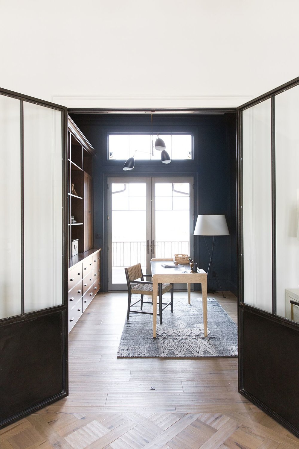 Moody mountain office with dark paneled walls, built-in, abstract artwork - Studio McGee Design