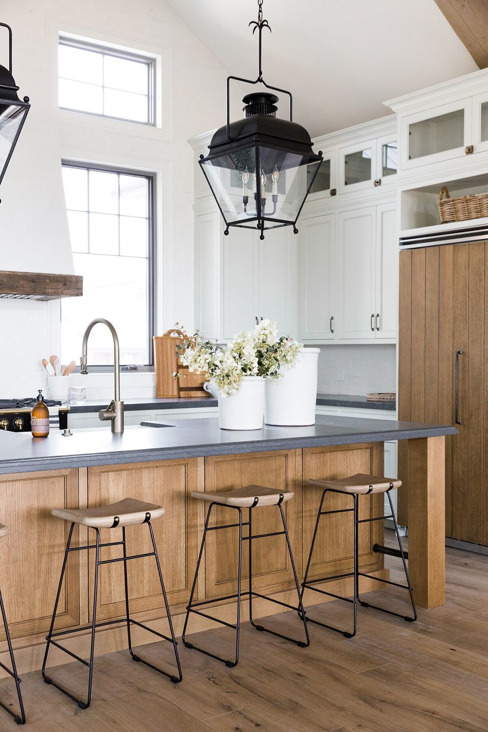 Refined, rustic kitchen with exposed wooden beams, hanging lanterns, painted white brick, oven range in mountain home - Studio McGee Design